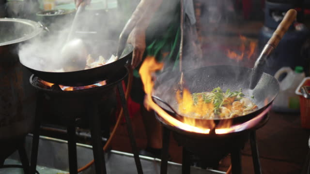 chef hand cooking with fire pan, street food - cultura tailandese video stock e b–roll