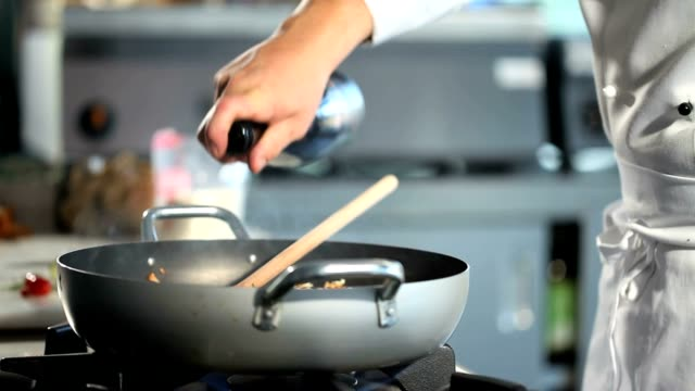 chef hands cooking food pouring wine in pan on cooker in restaurant kitchen close up video