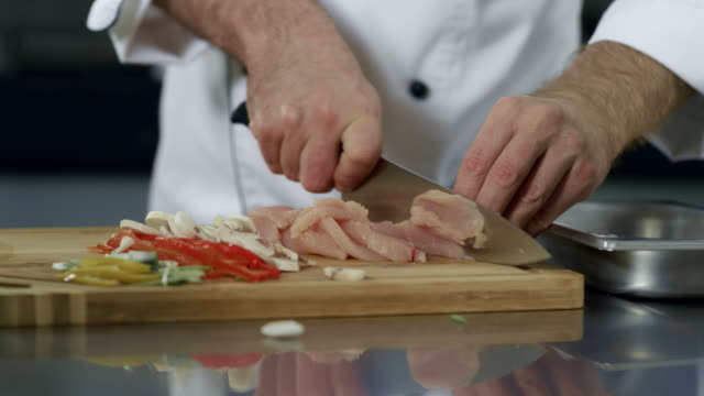 chef hands cutting meat at kitchen. closeup chef hands cutting chicken fillet - articoli casalinghi video stock e b–roll