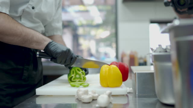 chef hands cutting pepper at commercial kitchen - peperone video stock e b–roll