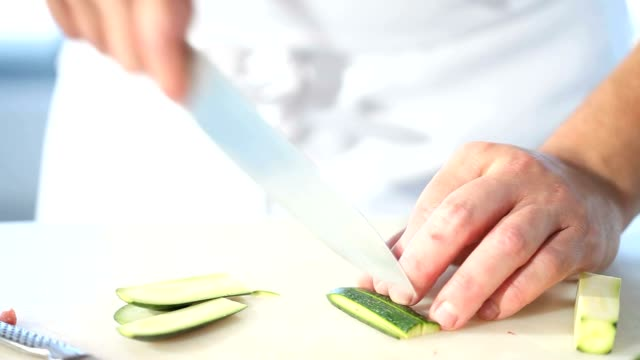 chef hands cutting zucchini in restaurant kitchen close up video