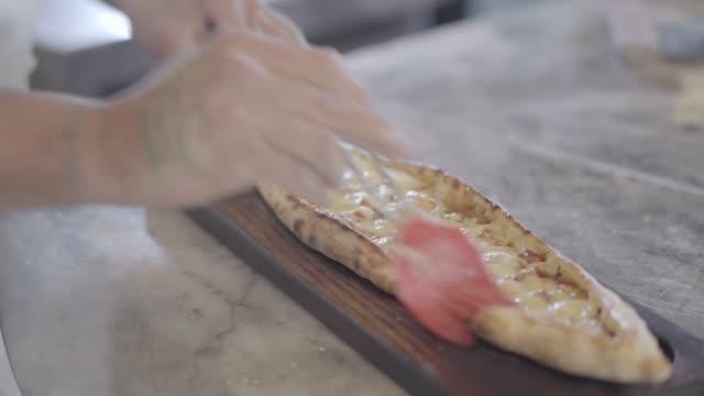 chef hands grease baked dough of turkish arabic food fatayer with olive oil - chleb pita filmów i materiałów b-roll