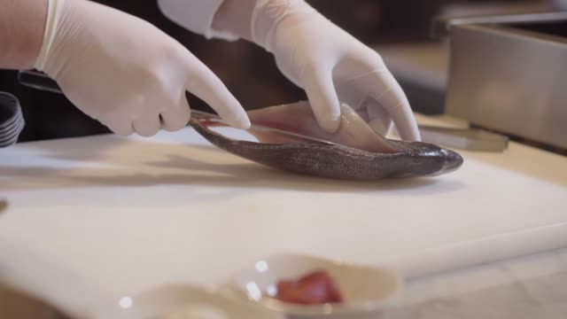 Chef hands in rubber gloves prepare raw fish over cutting board.