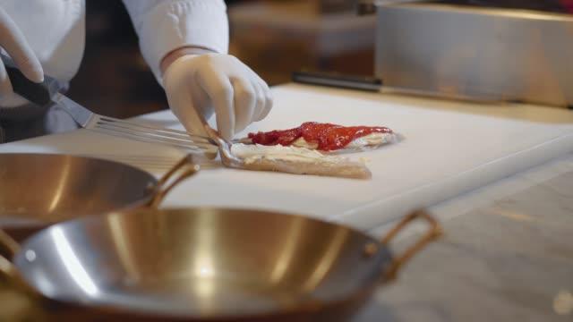 Chef hands prepare fish fillet over cutting board.