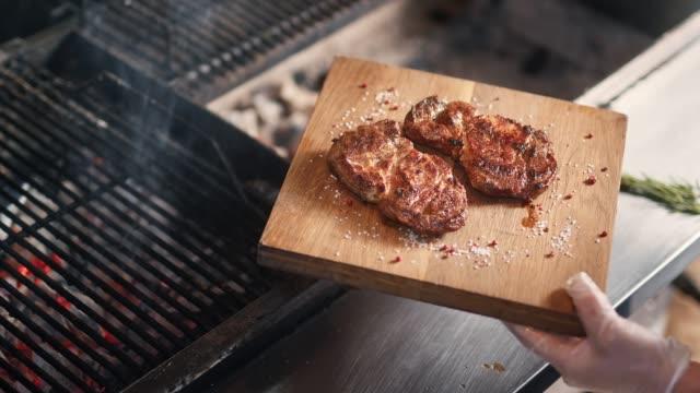 chef hands putting frying meat on wooden board serving herbs. close up shot on 4k red camera - готовый к употреблению стоковые видео и кадры b-roll
