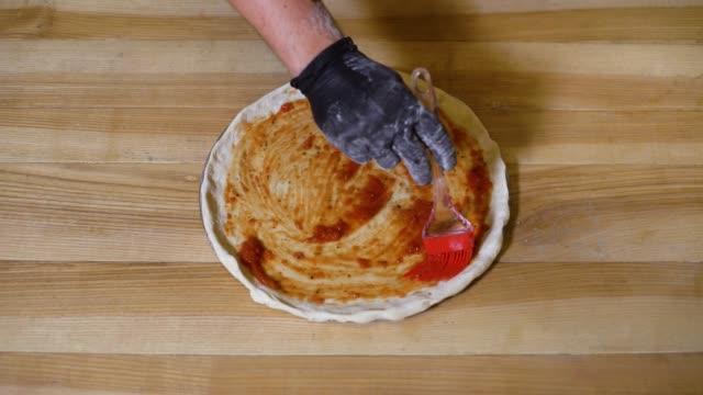 koch die hände, zutaten auf rohen teig pizza backen und mit großen metall-schaufel nehmen - selbstgemacht stock-videos und b-roll-filmmaterial