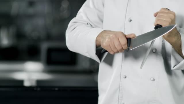 vídeos de stock, filmes e b-roll de mãos do cozinheiro chefe que afiam a faca no movimento lento. as mãos do close up cozinham o alimento na cozinha. - afiado