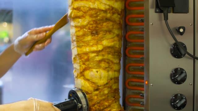 mani chef affettando carne doner da sputo rotante al negozio kebab - cultura turca video stock e b–roll