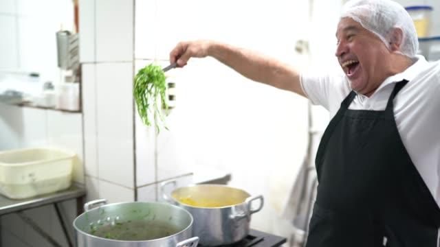 vídeos de stock e filmes b-roll de chef having fun and preparing food in industrial kitchen in restaurant - avental