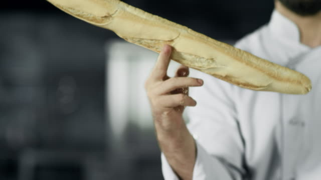 Chef having fun with french bread at kitchen. Closeup man hands play with bread