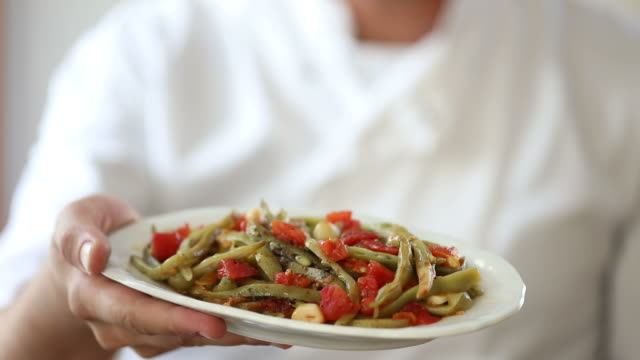 Chef holding a plate of green beans (zeytinyagli fasulye) video