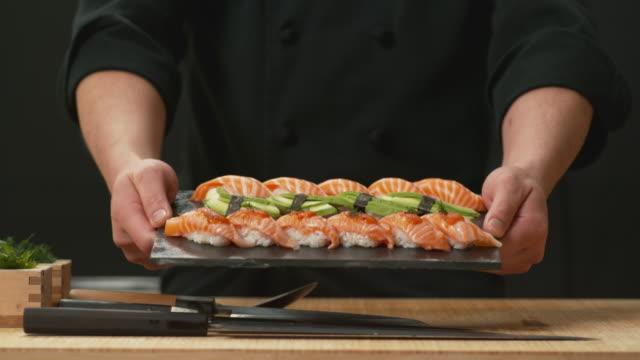 koch hält teller mit frischem sushi - sushi stock-videos und b-roll-filmmaterial