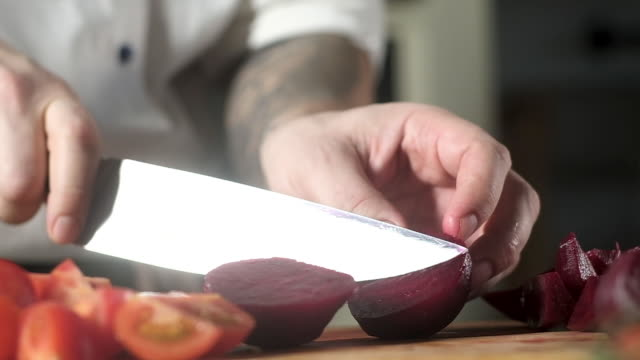 chef in kitchen cuts beetroot for salad. cooking salad with vegetables - chef triste video stock e b–roll