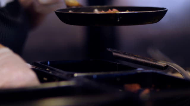 Chef in latex gloves preparing scrambled eggs in black frying pan on cooker.