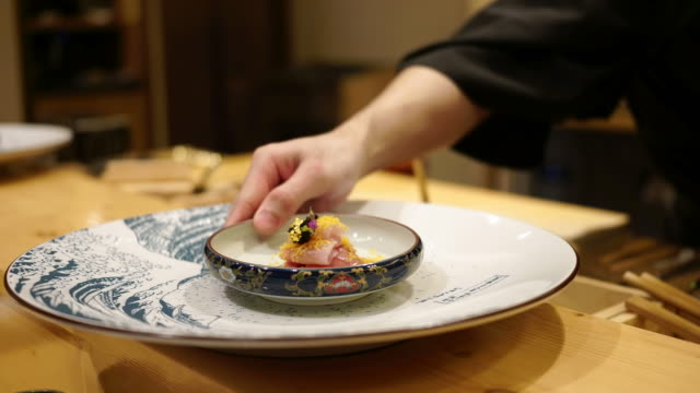 A Chef in the japanese restaurant is preparing and serving sashimi in the omagase food course, hand shot.