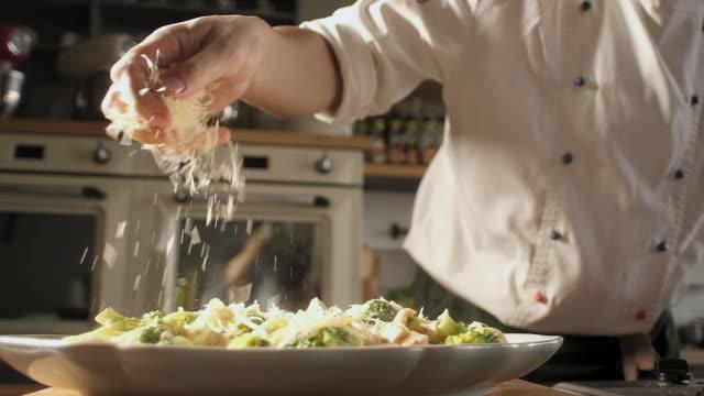 モダンなキッチンのシェフは、魚とパスタにすりおろしたパルメザンチーズを振りかけます - 料理人点の映像素材/bロール