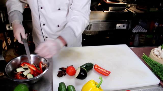 Chef in uniform slicing fresh vegetables in restaurant kitchen video