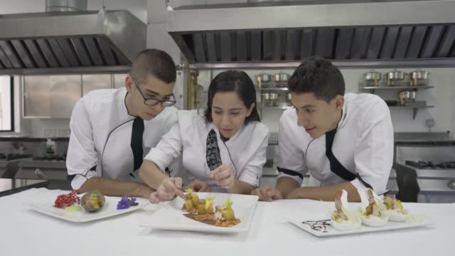 總廚導師教她的學生如何裝飾開胃菜 - 食物和飲品 個影片檔及 b 捲影像