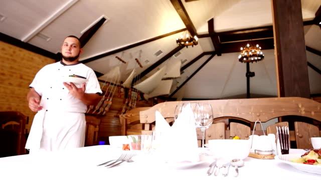 vídeos de stock, filmes e b-roll de chef convida-o para a mesa festiva no restaurante, o chef no salão de café tem um prato de comida, um retrato de um chef em um formulário de culinário, a tabela - primeira comunhão