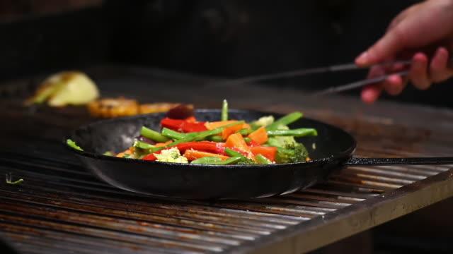 vídeos y material grabado en eventos de stock de chef está cocinando verduras en parrilla de carbón comercial. material de archivo fullhd de alta calidad. - social media