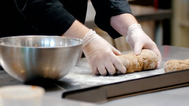 kitchen - chef is forming bread on the countertop - grindare video stock e b–roll