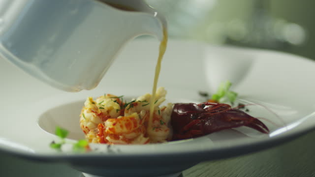 vídeos de stock e filmes b-roll de chef is garnish dish with lobster in luxury restaurant - servir comida e bebida