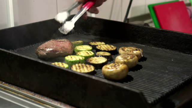 Chef is grilling a steak on the grill - vídeo