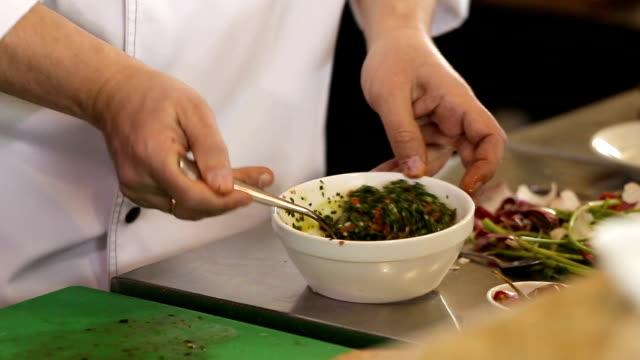 vídeos de stock, filmes e b-roll de o cozinheiro chefe está misturando um ingrediente a fazer algum molho - comida salgada