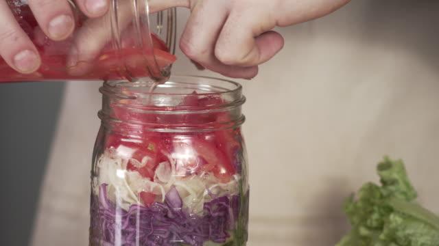 kocken lastning mason jar sallad med tomat och grön lök - konserveringsburk bildbanksvideor och videomaterial från bakom kulisserna