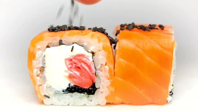 chef luxury sushi rolls japan cuisine restaurant presentation slowmotion on white black sesame seeds falling video
