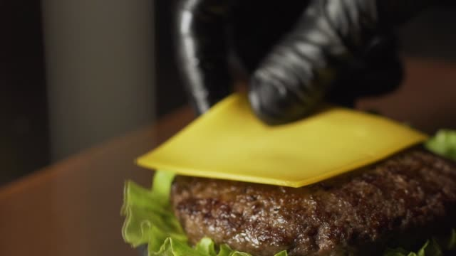 Chef making burger. Close-up shot of chef's hands preparing a delicious hamburger with beef rissole and cheese. Cooker putting a cutlet with cheese on bun, 4K slow motion Chef making burger. Close-up shot of chef's hands preparing a delicious hamburger with beef rissole and cheese. Cooker putting a cutlet with cheese on bun, 4K slow motion bun bread stock videos & royalty-free footage