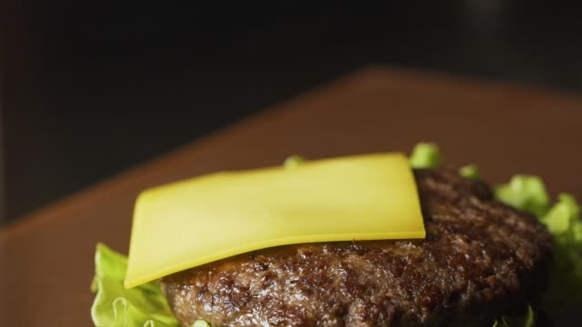 chef making burger. close-up shot of chef's hands preparing a delicious hamburger with beef rissole and cheese. cooker putting a cutlet with cheese on bun, 4k slow motion - guanto indumento sportivo protettivo video stock e b–roll
