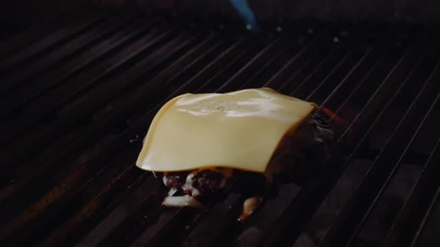 ハンバーガーを作るシェフ。クックは、ハンバーガーにチーズを溶かします。料理は、肉のカツレツのチーズを溶かすブロートーチを使用します。男はブロートーチを使用してハンバーガー� - チーズ 溶ける点の映像素材/bロール