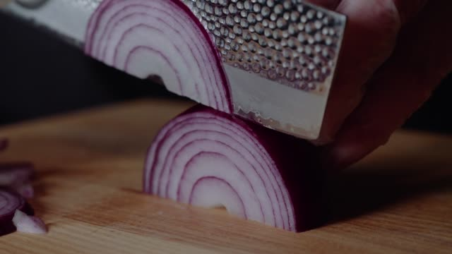 ハンバーガーを作るシェフ。男は、タマネギをスライスします。野菜のクイック切断。玉ねぎの半分が鳴る。フライパンのための弓。料理人の手。ハンバーガーやサラダ用の野菜を切る。ク� - 一切れ点の映像素材/bロール