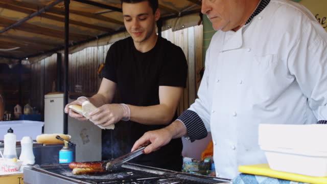 chef making burgers at outdoor market - video di bancarella video stock e b–roll