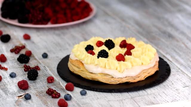 şef muhallebi ve kuş üzümü, ahududu, böğürtlen, yaban mersini ile puf böreği kek yapma. lezzetli tatlı. - muhallebi stok videoları ve detay görüntü çekimi