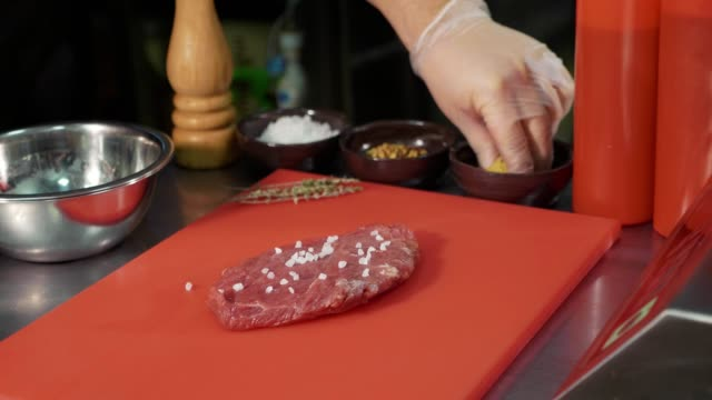 Chef marinating raw meat for preparing steak at commercial kitchen, close-up video