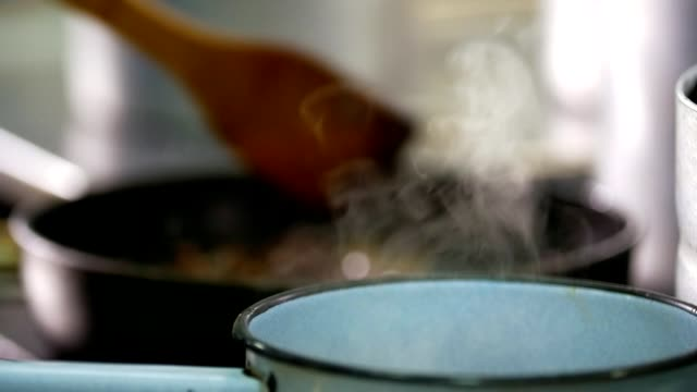 Chef mixes food in front of steam boiler video