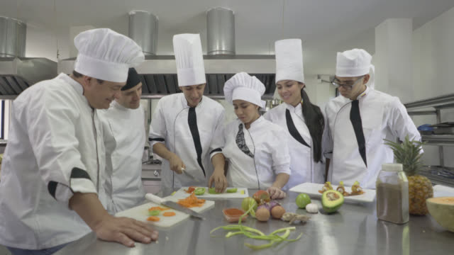 Chef observing his student chop a tomato  in class video