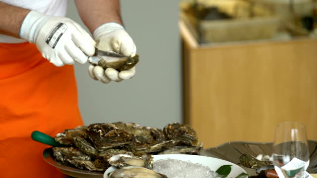 Chef opens fresh oysters for customers in the restaurant. video