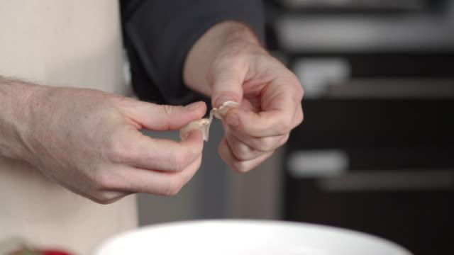 chef peeling garlic clove - aglio alliacee video stock e b–roll