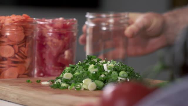 kocken plocka upp färsk hackad grön lök och sätta i mason jar för sallad - konserveringsburk bildbanksvideor och videomaterial från bakom kulisserna