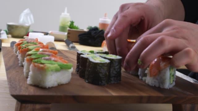 Chef placing sushi onto tray Chef placing sushi onto tray sashimi stock videos & royalty-free footage