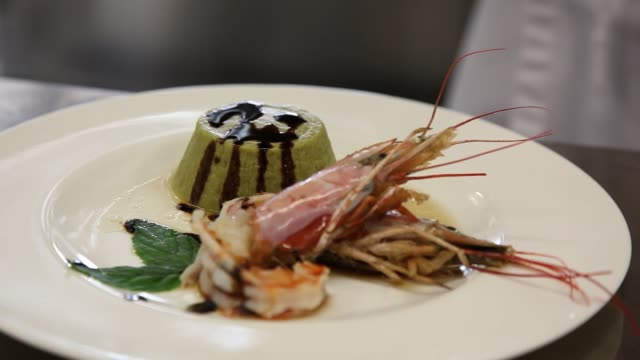 chef plating up a shrimp dish with a green tart in a restaurant kitchen - video
