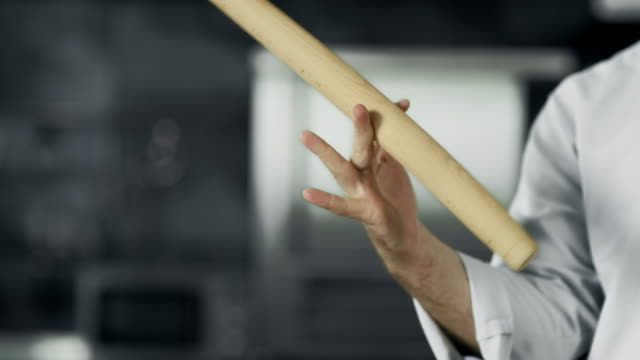 Chef playing with roller at workplace. Closeup man hands twist roller at kitchen