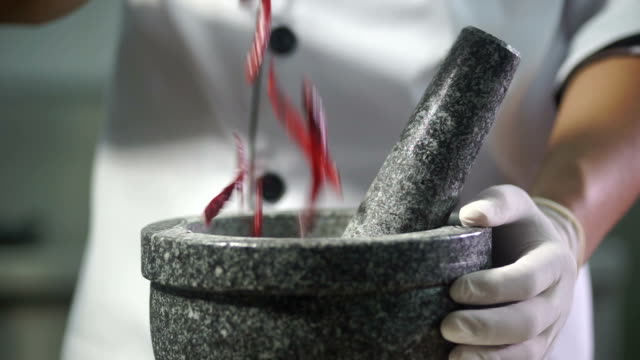 chef pounding and grinding chili in a mortar. - chilli con carne video stock e b–roll