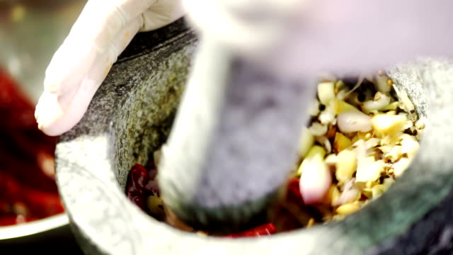 koch, hämmern und schleifen, gemischte gewürze und kräuter zutat von granit mörser und stößel für thailändisches essen. - chilli stock-videos und b-roll-filmmaterial