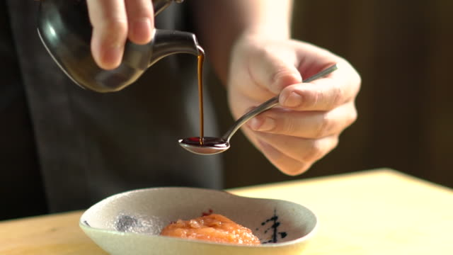 Chef pouring  Japanese sauce to a bowl with Japanese food in kitchen at the restaurant