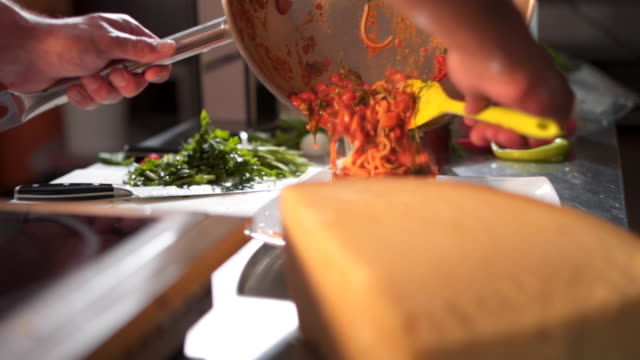 vídeos de stock e filmes b-roll de chef pouring spaghetii on plate - avental