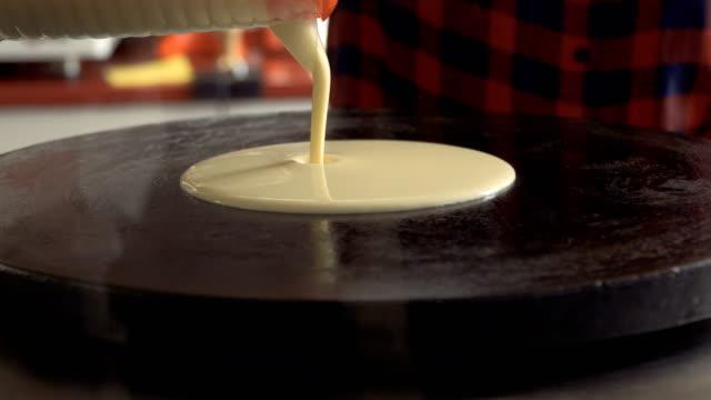 kocken häller flytande pannkaka degen på en het spis - crepes bildbanksvideor och videomaterial från bakom kulisserna